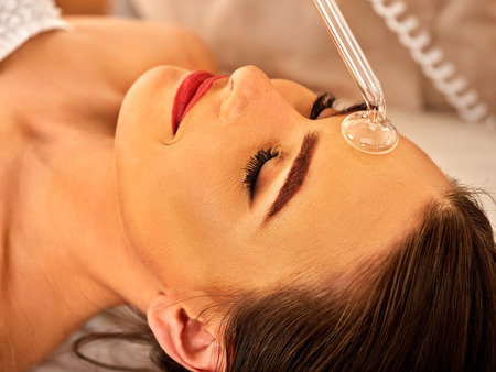 Photo for High frequency machine in spa salon. Young woman receiving electric darsonval facial massage after procedure at beauty room close up. - Royalty Free Image