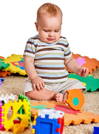 Foto für Baby making puzzle. Child jigsaw develops children. Kid holding big pieces and sitting on floor. Portrait of boy playing on soft babys mat in kindergarten. Logical tasks for development of child. - Lizenzfreies Bild