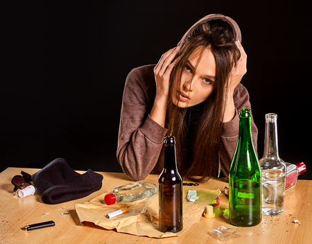 Foto de Woman alcoholism is social problem. Female drinking is cause of nervous stress. She in hood with rroup of green alcohol bottle in bad mood. Gap between a guy and a girl. - Imagen libre de derechos