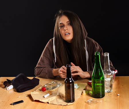 Foto de Woman alcoholism social problem. Female drinking is cause of nervous stress. She in hood with rroup of green alcohol bottle in bad mood. Mess on table. Depression after break with guy. - Imagen libre de derechos