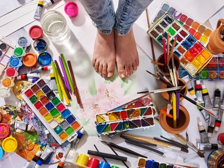 Photo for Authentic paint brushes still life on floor in art class school. Group of brush in clay jar. Barefooted female feet among creative mess. - Royalty Free Image