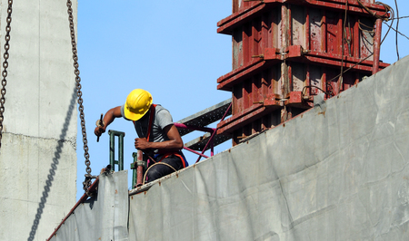 Photo pour Labor man working on construction site with helmet and safty equipment and covering the building with grey color vinyl and blue sky. - image libre de droit