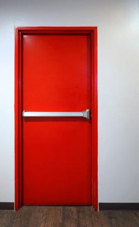 Foto de Emergency fire exit door red color metal material for safety protection and wood floor and white wall indoor building. - Imagen libre de derechos