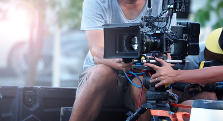 Foto de Blurry image of movie shooting or video production and film crew team with camera equipment at outdoor location and light flare effect. - Imagen libre de derechos