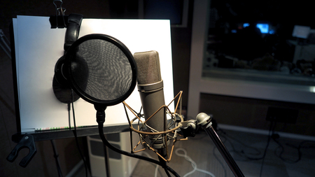 Photo for Microphone with pop filter and shock mount anti-vibration and note stand and tripod in music score studio production - Royalty Free Image