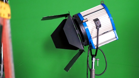 Photo for Big studio LED spotlight for video movie or photo film production with green screen background for chroma key technique in post lab process and professional equipment such as tripod and others. - Royalty Free Image