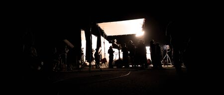 Photo for Silhouette images of video production behind the scene or b-roll or making of film shooting and movie crew team working in back of camera and lighting soft box equipment set at outdoor in the night - Royalty Free Image