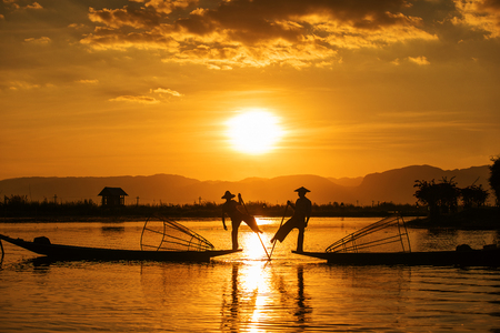 Foto de Inle fishermen are known for practising a distinctive rowing style which involves standing at the stern on one leg and wrapping the other leg around the boat paddle, Myanmar - Imagen libre de derechos