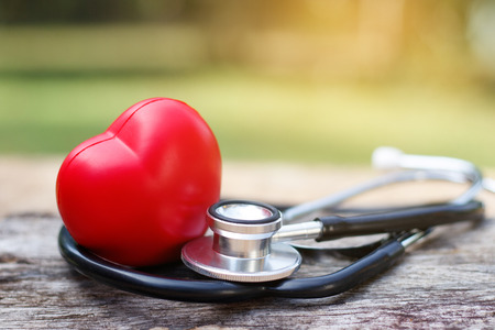 Photo pour Red heart and a stethoscope on wooden background. - image libre de droit
