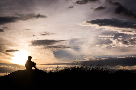 Photo pour Sad boy silhouette worried on the meadow at sunset ,Silhouette concept - image libre de droit