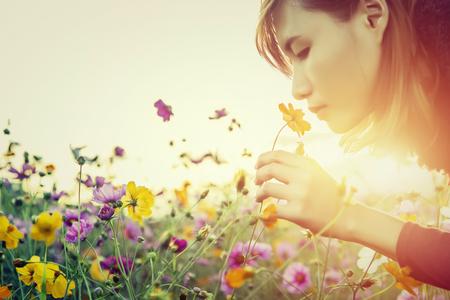 Foto de Pretty young woman smelling the flowers - Imagen libre de derechos