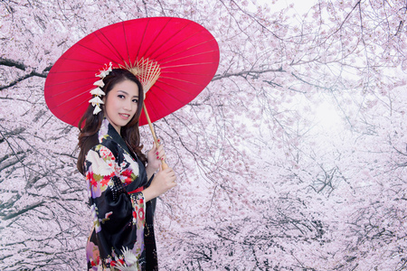 Foto de Beautiful young asian woman wearing traditional japanese kimono with red umbrella and cherry blossom. - Imagen libre de derechos