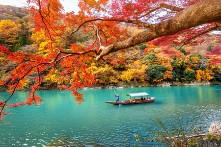 Foto de Boatman punting the boat at river. Arashiyama in autumn season along the river in Kyoto, Japan. - Imagen libre de derechos