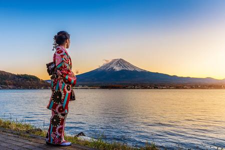 Photo pour Asian woman wearing japanese traditional kimono at Fuji mountain. Sunset at Kawaguchiko lake in Japan. - image libre de droit