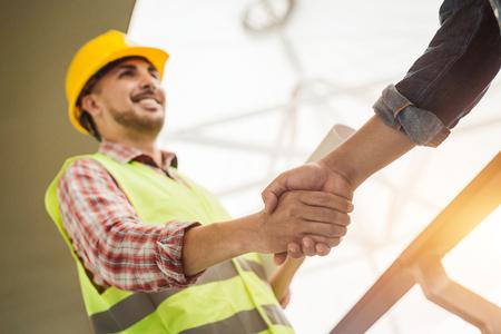 Foto de Engineer construction workers in protective helmets and vests are shaking hands while working in the office center - Imagen libre de derechos