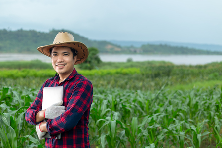 Foto de Young attractive farmer with laptop standing in corn field. - Imagen libre de derechos