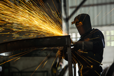 Foto de Masked workers and safety kits, Electric wheel grinding on steel structure and welders with multiple sparks in factory. - Imagen libre de derechos