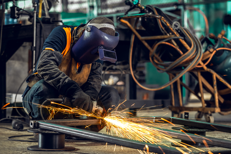 Photo pour Masked workers and safety kits, Electric wheel grinding on steel structure and welders with multiple sparks in factory. - image libre de droit