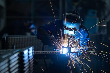 Foto de Workers wearing industrial uniforms and Welded Iron Mask at Steel welding plants, industrial safety first concept. - Imagen libre de derechos