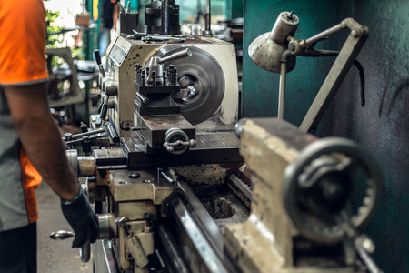 Photo pour LATHE MACHIN, Worker in uniform operating in manual lathe in metal industry factory. - image libre de droit