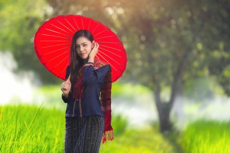 Foto de Beautiful Thai girl in traditional dress costume red umbrella, Thai Woman in Traditional Costume of Thailand. - Imagen libre de derechos