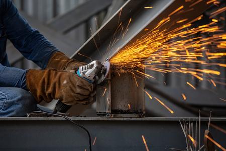 Foto de Electric wheel grinding on steel structure and welders with multiple sparks in factory. - Imagen libre de derechos