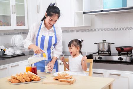 Foto de preparation of a family breakfast. Asian mother and baby daughter cook breakfast in morning. - Imagen libre de derechos
