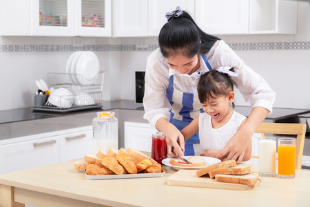 Photo for eating and people concept - Asian happy mother and daughter having breakfast at home. - Royalty Free Image