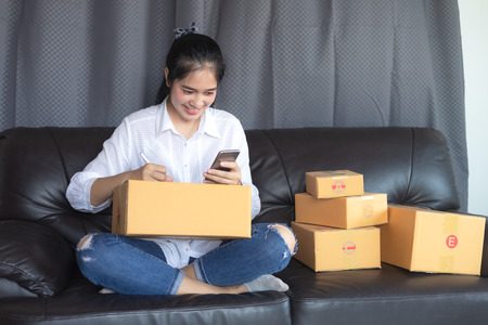 Photo pour Asian girls get the order by phone, Online shopping young start small business in a cardboard box at work. The seller prepares the delivery box for the customer, online sales, or ecommerce. - image libre de droit