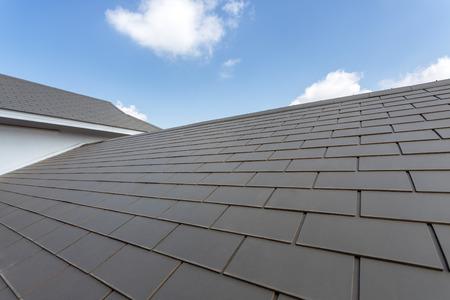 Foto de Slate roof against blue sky, Gray tile roof of construction house with blue sky and cloud background - Imagen libre de derechos