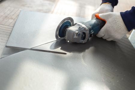 Foto de Worker cutting a tile using an angle grinder at construction site - Imagen libre de derechos