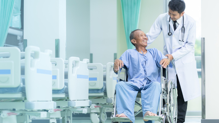 Foto de Asian patient in wheelchair sitting in hospital corridor with Asian male doctor, Medical equipment concept. - Imagen libre de derechos