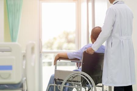 Foto de Asian patient in wheelchair sitting in hospital corridor with Asian male doctor, Medical equipment concept. - Imagen libre de derechos