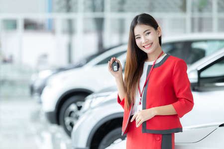 Photo pour Asian saleswoman giving car key over auto show background, auto business, car sale, gesture and people concept - happy businesswoman. - image libre de droit