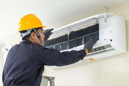 Photo pour Male technician repairing air conditioner safety uniform indoors. - image libre de droit