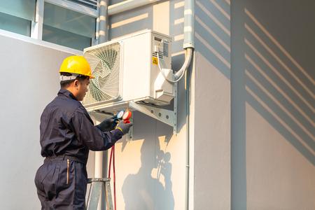 Photo pour Male technician repairing air conditioner safety uniform, Technician vacuum pump evacuates and checking new air conditioner. - image libre de droit