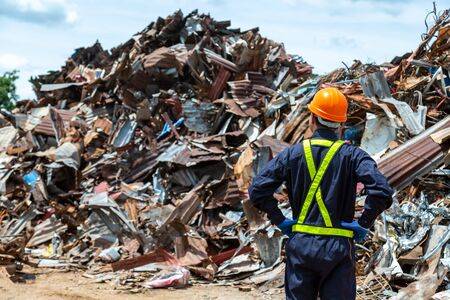 Foto de workers in landfill dumping, Garbage engineer, recycling, wearing a safety suit standing in the outdoor recycling center have a metal scrap pile in the background. - Imagen libre de derechos