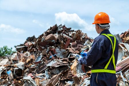 Foto de workers in landfill dumping, Garbage engineer, recycling, wearing a safety suit standing to check the amount of recycled metal scrap. - Imagen libre de derechos
