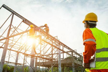 Foto de A construction worker control in the construction of roof structures on construction site and sunset background - Imagen libre de derechos