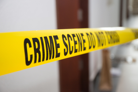 Photo pour crime scene tape in front of room door with blurred background - image libre de droit