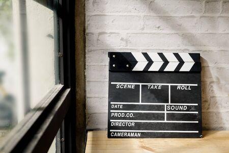 Photo pour movie clapper on wood desk with windows light. - image libre de droit