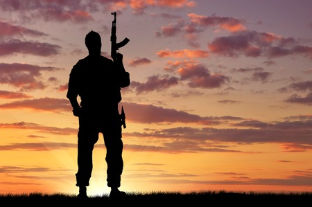 Photo for Silhouette of soldier with a gun on a background of sunset - Royalty Free Image