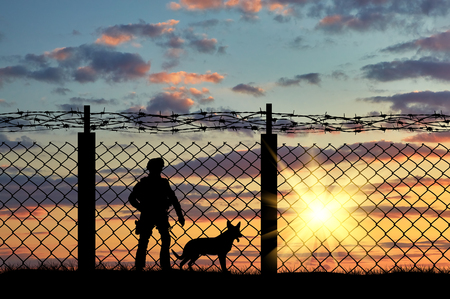 Foto de Silhouette of a soldier on the border with a fence and a dog at sunset - Imagen libre de derechos