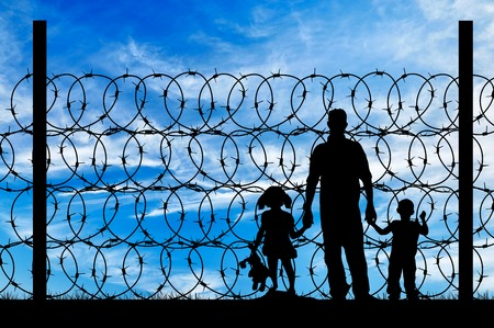 Foto de Silhouette of a family with children of refugees and fence with barbed wire on the background of the beautiful sky - Imagen libre de derechos