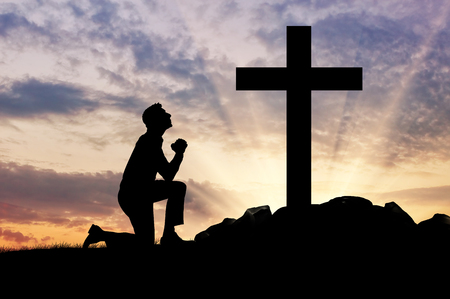Photo pour concept of religion. Silhouette of a man praying before a cross at sunset - image libre de droit