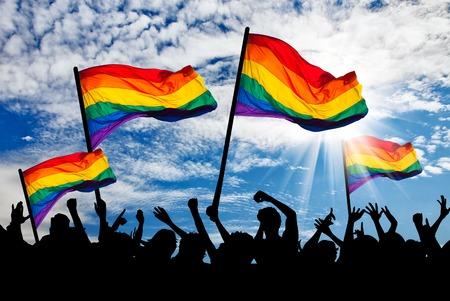 Foto de Silhouette of a parade of gays and lesbians with a rainbow flag - Imagen libre de derechos