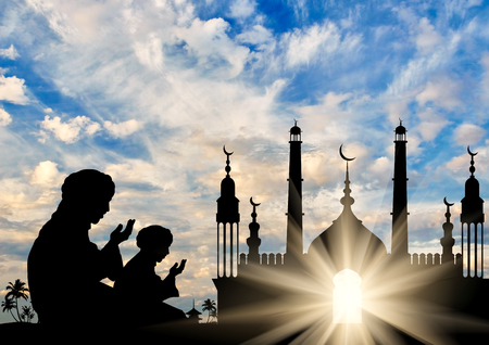 Photo pour Concept of the Islamic religion. Silhouette of two men praying on the background of the town hall at dawn - image libre de droit