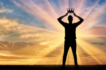 Photo for Concept of narcissism and selfishness. Silhouette of a selfish and narcissistic man reconciling his own crown - Royalty Free Image