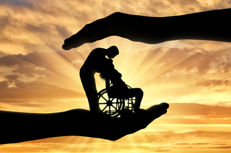Foto de Silhouettes of a happy disabled woman in a wheelchair with a man who kisses her. The concept of support and assistance for people with disabilities - Imagen libre de derechos