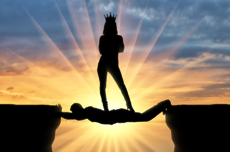 Photo pour Selfish woman with a crown standing on a man in the form of a bridge over an abyss. Concept of selfishness and personal interest - image libre de droit
